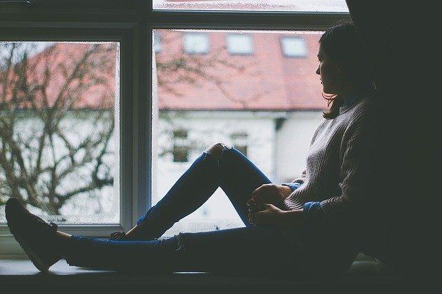 smutná žena kouká z okna